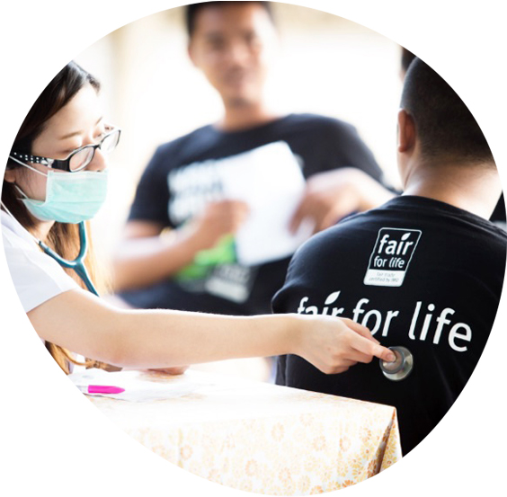Woman physician with a stethoscope giving a boy wearing a Fair for Life t-shirt a check up